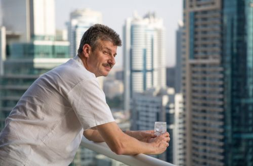 Expat man on balcony thinking about Tax Cuts and Jobs Act