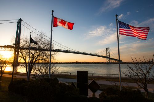 The Ambassador Bridge linkink Detroit, Michigan, USA with Windsor, Ontario, Canada. The national flags of the USA and of Canada are notable in the foreground.