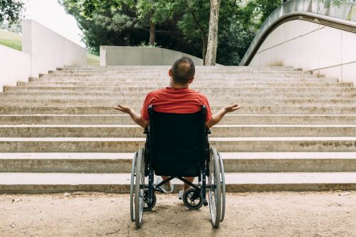 disabled man in a wheelchair stopped in front of a staircase